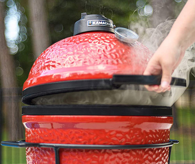 Smoke coming out of a red Kamodo Joe Jr Charcoal Grill